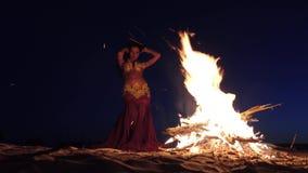 Νύχτα η κοιλιά χορών κοριτσιών που χορεύει στην άμμο, έχει μια φωτεινή εξάρτηση απόθεμα βίντεο