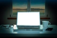 Νύχτα - παράθυρο και φορητός προσωπικός υπολογιστής με την κενή οθόνη Στοκ Φωτογραφίες