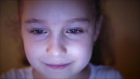 Νύχτα που αυξάνεται ενός χαριτωμένου καυκάσιου μικρού κοριτσιού κοντά του προσώπου ενός παιδιού που βλέπει ένα PC ταμπλετών με μι απόθεμα βίντεο