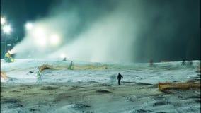 Νύχτα που κάνει σκι στις κλίσεις σκι και τα πυροβόλα χιονιού φιλμ μικρού μήκους