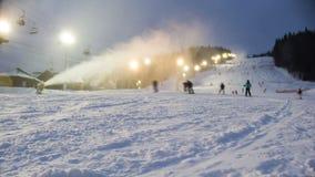 Νύχτα που κάνει σκι στις κλίσεις σκι και τα πυροβόλα χιονιού απόθεμα βίντεο