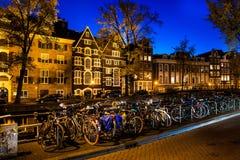 Νύχτα που πυροβολείται της πόλης, πολλά ποδήλατα στη γέφυρα στο κανάλι του Άμστερνταμ, Κάτω Χώρες Στοκ φωτογραφίες με δικαίωμα ελεύθερης χρήσης