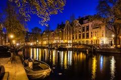 Νύχτα που πυροβολείται της πόλης, πολλά ποδήλατα στη γέφυρα στο κανάλι του Άμστερνταμ, Κάτω Χώρες Στοκ Εικόνες