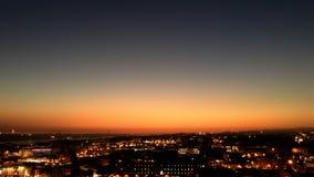 Νύχτα πόλεων από το σημείο άποψης πάνω από το λόφο στο όμορφο sunse Στοκ Εικόνα