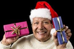 Ξέγνοιαστος, χαμογελώντας ηληκιωμένος που προσφέρει δύο δώρα στοκ εικόνες με δικαίωμα ελεύθερης χρήσης