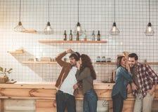 Ξένοιαστα κορίτσια που μιλούν με τους τύπους στην καφετέρια Στοκ Εικόνες
