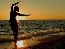 Ξένοιαστη γυναίκα που χορεύει στο ηλιοβασίλεμα στην παραλία στοκ φωτογραφία