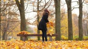 Ξένοιαστη γυναίκα στο πάρκο φθινοπώρου που χορεύει και που ρίχνει τα φύλλα φιλμ μικρού μήκους