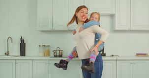 Ξένοιαστη μητέρα piggybacking το συγκινημένο παιδί στην κουζίνα φιλμ μικρού μήκους