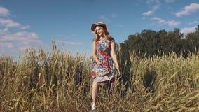 Ξένοιαστη νέα γυναίκα που περπατά μέσω του τομέα σε ένα φωτεινό φόρεμα και ένα καπέλο αχύρου κίνηση αργή φιλμ μικρού μήκους