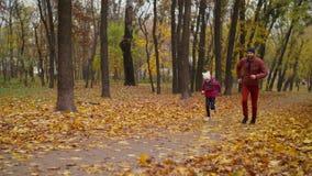 Ξένοιαστοι πατέρας και κόρη που τρέχουν στο πάρκο φθινοπώρου φιλμ μικρού μήκους