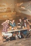 Ξένοιαστοι τύποι και κορίτσια που μιλούν στη καφετερία Στοκ φωτογραφία με δικαίωμα ελεύθερης χρήσης