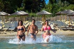Ξένοιαστοι φίλοι που έχουν τη διασκέδαση τρέχοντας στη θάλασσα στοκ φωτογραφία με δικαίωμα ελεύθερης χρήσης