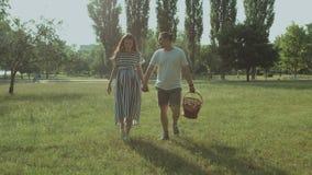 Ξένοιαστο έγκυο ζεύγος που περπατά στο πάρκο στο ηλιοβασίλεμα φιλμ μικρού μήκους