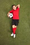 Ξένοιαστο αγόρι που βάζει στη χλόη και που κρατά το ποδόσφαιρο Στοκ Εικόνες