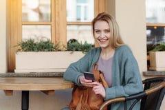 Ξένοιαστο ξανθό κορίτσι που στηρίζεται με τη συσκευή έξω Στοκ Εικόνα