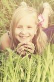 Ξένοιαστο χαμογελώντας ξανθό κορίτσι στη χλόη Στοκ εικόνες με δικαίωμα ελεύθερης χρήσης