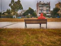 Ξένος με μια κόκκινη συνεδρίαση παλτών σε έναν πάγκο σε ένα πάρκο μια βροχερή ημέρα ενάντια σε έναν δραματικό ουρανό Στοκ εικόνες με δικαίωμα ελεύθερης χρήσης
