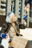 Ξένος που δίνει μεγάλο burger κρέατος στους χαμογελώντας ανακουφισμένους αστέγους Στοκ Εικόνες