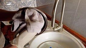 Ξήρανση γυναικών από τα πιάτα στην κουζίνα με τα γάντια απόθεμα βίντεο