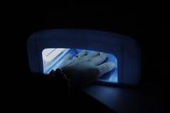 Ξήρανση θηλυκής ουσία νυχιών στο στεγνωτήρα υπεριώδους φωτός Στοκ Εικόνες
