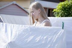 Ξήρανση κοριτσιών εφήβων στα άσπρα φύλλα σχοινιών στον ήλιο στοκ εικόνες