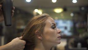 Ξήρανση Hairstylist μακρυμάλλης της νέας γυναίκας hairstyling hairdressing στο σαλόνι Κομμωτής που χρησιμοποιεί το στεγνωτήρα τρί απόθεμα βίντεο
