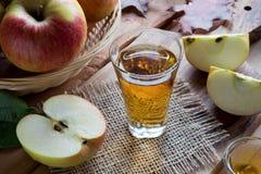 Ξίδι μηλίτη της Apple σε ένα γυαλί, με τα μήλα στο υπόβαθρο Στοκ φωτογραφία με δικαίωμα ελεύθερης χρήσης