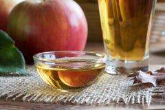 Ξίδι μηλίτη της Apple σε ένα κύπελλο γυαλιού, με τα μήλα στο backgrou Στοκ Φωτογραφίες