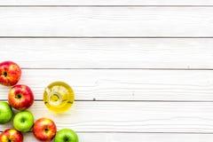 Ξίδι μηλίτη της Apple στο μπουκάλι μεταξύ των φρέσκων μήλων στο άσπρο ξύλινο διάστημα αντιγράφων άποψης υποβάθρου τοπ Στοκ φωτογραφίες με δικαίωμα ελεύθερης χρήσης