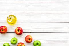 Ξίδι μηλίτη της Apple στο μπουκάλι μεταξύ των φρέσκων μήλων στο άσπρο ξύλινο διάστημα αντιγράφων άποψης υποβάθρου τοπ Στοκ εικόνα με δικαίωμα ελεύθερης χρήσης