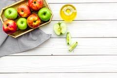Ξίδι μηλίτη της Apple στο μπουκάλι μεταξύ των φρέσκων μήλων στο άσπρο ξύλινο διάστημα αντιγράφων άποψης υποβάθρου τοπ Στοκ Εικόνες