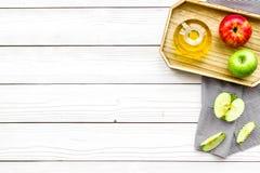 Ξίδι μηλίτη της Apple στο μπουκάλι μεταξύ των φρέσκων μήλων στο άσπρο ξύλινο διάστημα αντιγράφων άποψης υποβάθρου τοπ Στοκ Φωτογραφία