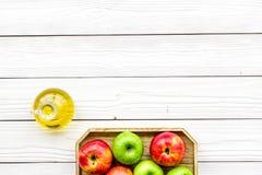 Ξίδι μηλίτη της Apple στο μπουκάλι μεταξύ των φρέσκων μήλων στο άσπρο ξύλινο διάστημα αντιγράφων άποψης υποβάθρου τοπ Στοκ Εικόνα