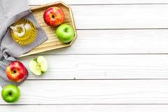 Ξίδι μηλίτη της Apple στο μπουκάλι μεταξύ των φρέσκων μήλων στο άσπρο ξύλινο διάστημα αντιγράφων άποψης υποβάθρου τοπ Στοκ εικόνες με δικαίωμα ελεύθερης χρήσης