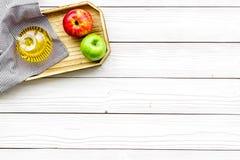 Ξίδι μηλίτη της Apple στο μπουκάλι μεταξύ των φρέσκων μήλων στο άσπρο ξύλινο διάστημα αντιγράφων άποψης υποβάθρου τοπ Στοκ Φωτογραφίες
