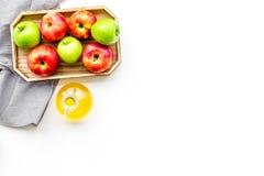 Ξίδι μηλίτη της Apple στο μπουκάλι μεταξύ των φρέσκων μήλων στο άσπρο διάστημα αντιγράφων άποψης υποβάθρου τοπ Στοκ Εικόνα