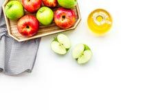 Ξίδι μηλίτη της Apple στο μπουκάλι μεταξύ των φρέσκων μήλων στο άσπρο διάστημα αντιγράφων άποψης υποβάθρου τοπ Στοκ φωτογραφία με δικαίωμα ελεύθερης χρήσης