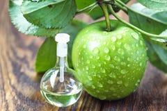 Ξίδι της Apple στο βάζο γυαλιού με τα ώριμα πράσινα φρούτα Μπουκάλι του οργανικού ξιδιού μήλων στο ξύλινο υπόβαθρο υγιής οργανικό Στοκ Εικόνα