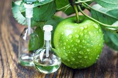 Ξίδι της Apple στο βάζο γυαλιού με τα ώριμα πράσινα φρούτα Μπουκάλι του οργανικού ξιδιού μήλων στο ξύλινο υπόβαθρο υγιής οργανικό Στοκ Εικόνες