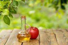 Ξίδι της Apple στο μπουκάλι γυαλιού και φρέσκο κόκκινο μήλο στον ξύλινο κάπρο Στοκ Εικόνες