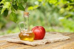 Ξίδι της Apple στο μπουκάλι γυαλιού και φρέσκο κόκκινο μήλο στον ξύλινο κάπρο Στοκ εικόνες με δικαίωμα ελεύθερης χρήσης