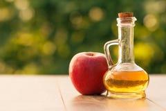 Ξίδι της Apple στο μπουκάλι γυαλιού και φρέσκο κόκκινο μήλο στον ξύλινο κάπρο Στοκ Εικόνα