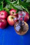 Ξίδι μηλίτη της Apple Ένα μπουκάλι γυαλιού στο μπλε υπόβαθρο κόκκινο μήλων Στοκ φωτογραφίες με δικαίωμα ελεύθερης χρήσης