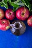 Ξίδι μηλίτη της Apple Ένα μπουκάλι γυαλιού στο μπλε υπόβαθρο κόκκινο μήλων Τοπ όψη Στοκ φωτογραφίες με δικαίωμα ελεύθερης χρήσης