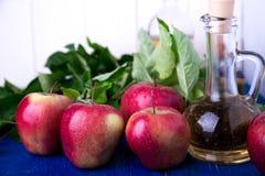 Ξίδι μηλίτη της Apple Ένα μπουκάλι γυαλιού στο μπλε υπόβαθρο κόκκινο μήλων Στοκ Εικόνες