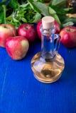 Ξίδι μηλίτη της Apple Ένα μπουκάλι γυαλιού στο μπλε υπόβαθρο κόκκινο μήλων Στοκ Φωτογραφία