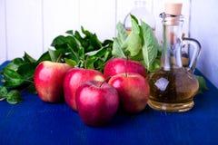 Ξίδι μηλίτη της Apple Ένα μπουκάλι γυαλιού στο μπλε υπόβαθρο κόκκινο μήλων Στοκ φωτογραφία με δικαίωμα ελεύθερης χρήσης