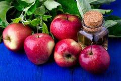 Ξίδι μηλίτη της Apple Ένα μπουκάλι γυαλιού στο μπλε υπόβαθρο κόκκινο μήλων Στοκ Εικόνα