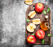 Ξίδι μηλίτη της Apple με τα φρέσκα μήλα στον τέμνοντα πίνακα Στοκ Εικόνες